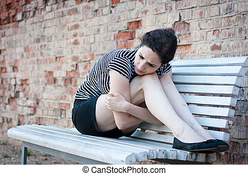 Depressed young woman sitting on a bench in an urban area