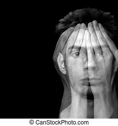 Depression and Fear - Young male covering his face with his...