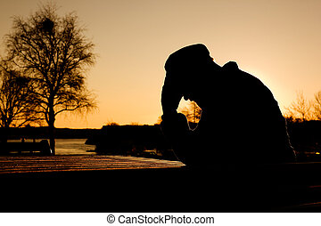 Depression - A depressed thoughtful man by the water at...