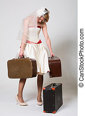 Depressive bride with suitcases on a white background in the studio