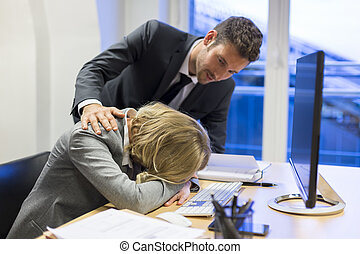 Depressive businesswoman in office with his colleague