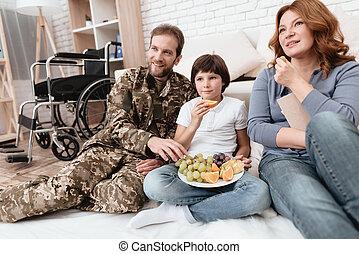 der, familie, spends, zeit, zusammen., a, behinderten, vater, in, militärische uniform, gleichfalls, essende, früchte, mit, seine, family.