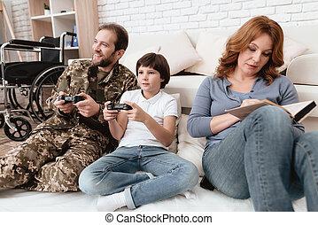 der, familie, spends, zeit, zusammen., a, behinderten, vater, in, militärische uniform, gleichfalls, spielende , mit, seine, sohn, auf, console.