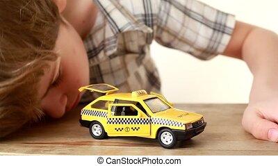 der, junge, spielende , mit, spielzeug, taxifahrzeuge, auto