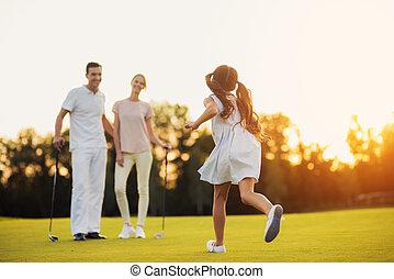 der, m�dchen, läufe, über, der, golfplatz, gegen, der, mann frau, wer, stehen, vor, sie, und, golfschläger