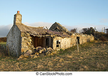 Derelict abandoned building, cottage, with crumbling walls and roof on grass with a blue sky.