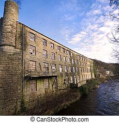 Abandoned and derelict Victorian Mill / Factory on the river bank in West Yorkshire