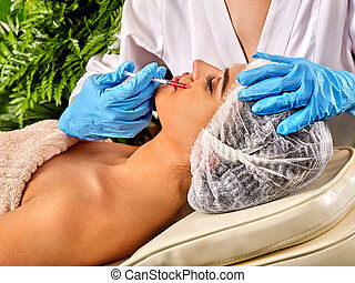Dermal fillers lips of woman in spa salon with beautician. -...