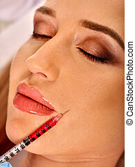 Dermal fillers of woman in spa salon with beautician.