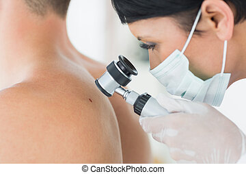 Dermatologist examining mole on patient - Closeup of...