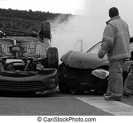 Desaturated close up image of firemen at the scene of a serious car accident on a dark, rainy fall day.