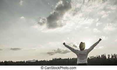 Desaturated image of victory, power and success - businessman standing with his arms reaching up towards sky with his hand making fists as he celebrates his personal and business achievement.