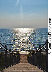 Stairs down to Lake Michigan from the top of a sand dune with sailboat in distance.