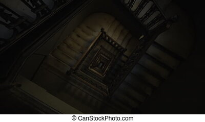 Descending top down view of old wooden staircase leading in the dark 4K