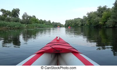 Descent on the river on kayaks among thicket, view from nose...
