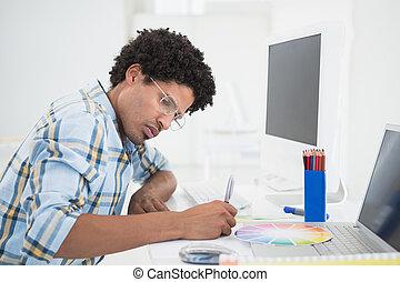 desenhista, seu, jovem, trabalhando, escrivaninha