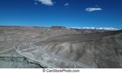 Desert barren landscape with two lane road and majestic blue...