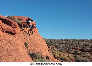 Desert Descent - A rider drops down a steep sandstone...
