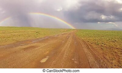 desert driving on a muddy road with a rainbow in the back