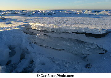 Desert ice floe to ice floe to the horizon line in the light of the morning sun
