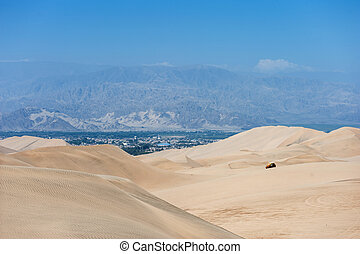 Desert in Huacachina, Peru. Buggy and dunes in background