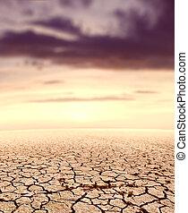 Desert landscape and sunset.Cracked soil