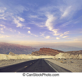 Desert road leading through Death Valley National Park, California USA.