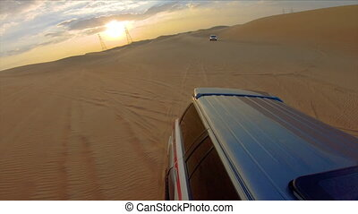 Desert safari off road, cockpit view from cabin or car, view to sunset. Jeep or SUV or 4x4 vehicle rides on desert dune barkhan or sand-dune.