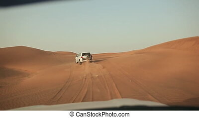 Desert Safari SUVs bashing through the arabian sand dunes. View from the car 8.