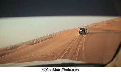 Desert Safari SUVs bashing through the arabian sand dunes. View from the car 9.
