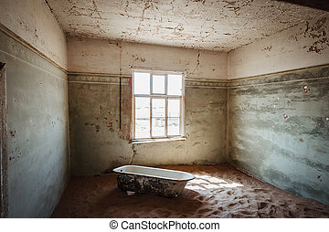 Desert sand entering old abandoned building with bath tub