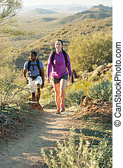 Desert Trail Hike - Young couple hiking outdoors on a trail...