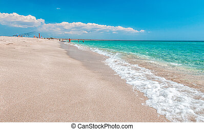 Deserted beach with white sand and crystal clear azure sea. blurred background for your text. concept of travel, ideal place for summer vacation by the sea in a safe place. Copy space.