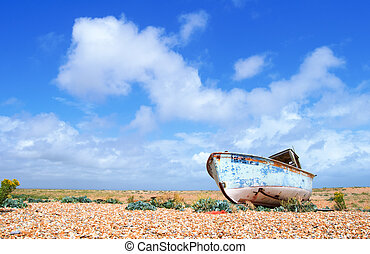 an old broken abandoned boat on a deserted shingle beach