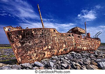 Deserted rusty ship on a rocky beach