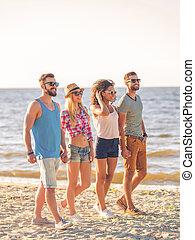 desfrutando, verão, junto., dois, sorrindo, pares jovens, segurar passa, ao andar, ao longo, a, praia, com, mar, em, a, fundo