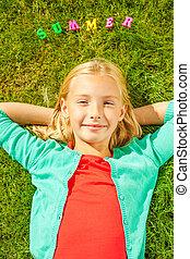 desfrutando, verão, time., vista superior, de, cute, menininha, segurar passa, atrás de, cabeça, sorrindo, enquanto, mentindo, ligado, a, grama verde, com, plástico, coloridos, letras, deitando, sobre, dela, cabeça