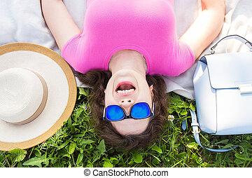 desgastar, engraçado, conceito, óculos de sol, parque, topo, -, jovem, feriados, mulher, verão, divertimento, retrato, capim, mentindo