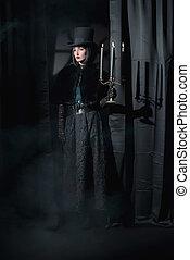 desgastar, mulher, feiticeira, candlestick., moda, gótico, segurando, hat., capa, pretas