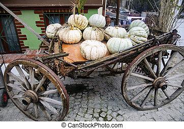 Designed for decorating, Several large pumpkins on an old car.