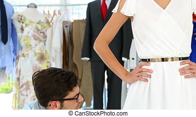 Designer adjusting hemline of dress on model in his studio