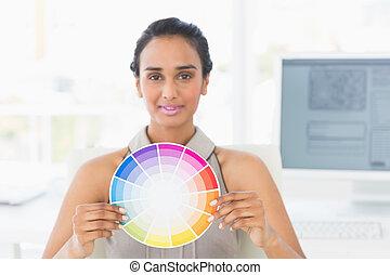 Designer at her desk showing colour wheel to camera