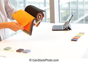 designer browsing coloful textiles in sample book - interior design situation