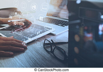 Designer Businessman hand using smart phone, mobile payments online shopping, omni channel, digital tablet docking keyboard computer in modern office on wooden desk, virtual interface icons screen