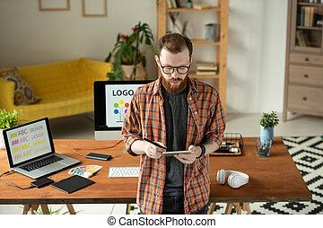 Designer checking sketch on tablet