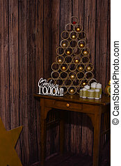 Designer Christmas tree on the table on a wooden background with large white candles
