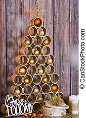 Designer Christmas tree with toys and gifts on a wooden background with candles