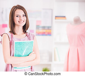 Designer clothing - Female fashion designer looking at...