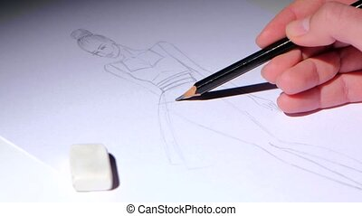 Designer creates fashion dress sketch, sitting at a white table. Close up