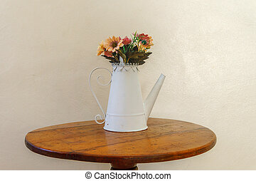 creative vase in the form of a white teapot with flowers on the table
